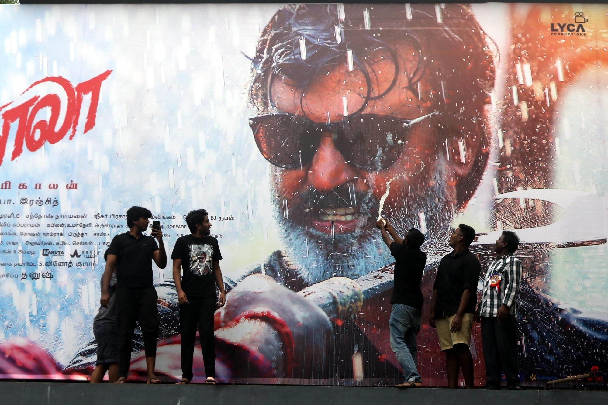 "Chennai: Fans wash a poster of actor Rajinikanth with milk after release of his film ""Kaala"" in Chennai on June 7, 2018. (Photo: IANS)"
